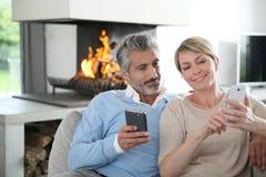 Couples d'une cinquantaine d'années de sourire utilisant des smartphones Photographie stock