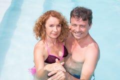 Couples d'une cinquantaine d'années gais dans une piscine Images libres de droits