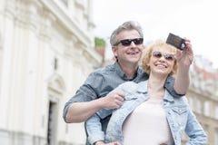 Couples d'une cinquantaine d'années heureux dans des lunettes de soleil prenant l'autoportrait dehors Photo stock