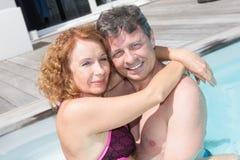 Couples d'une cinquantaine d'années heureux dans une piscine Photo libre de droits