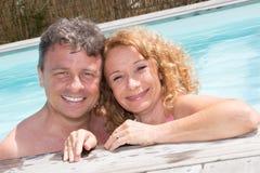 Couples d'une cinquantaine d'années heureux dans une piscine Photos stock