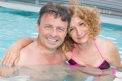 Couples d'une cinquantaine d'années heureux dans une piscine Images stock
