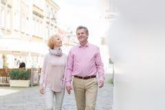 Couples d'une cinquantaine d'années heureux parlant tout en marchant dans la ville Photos stock