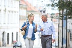 Couples d'une cinquantaine d'années heureux regardant l'un l'autre tout en tenant des cornets de crème glacée dans la ville Photos libres de droits