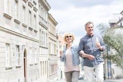 Couples d'une cinquantaine d'années heureux tenant des cornets de crème glacée tout en marchant dans la ville Image libre de droits