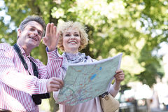 Couples d'une cinquantaine d'années heureux tenant la carte dans la ville Photos stock