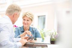 Couples d'une cinquantaine d'années heureux utilisant le téléphone portable au café de trottoir Image libre de droits