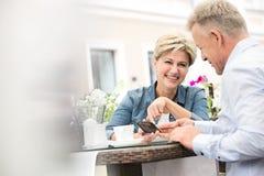 Couples d'une cinquantaine d'années heureux utilisant le téléphone portable au café de trottoir Photographie stock libre de droits