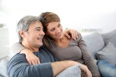 Couples d'une cinquantaine d'années regardant la TV Photos stock