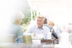 Couples d'une cinquantaine d'années se reposant au café de trottoir le jour ensoleillé Images stock