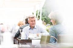 Couples d'une cinquantaine d'années se reposant au café de trottoir le jour ensoleillé Image libre de droits
