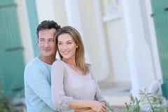 Couples d'une cinquantaine d'années se tenant et souriant devant la maison photographie stock libre de droits