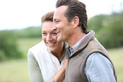 Couples d'une cinquantaine d'années sereins sur la campagne Photo stock