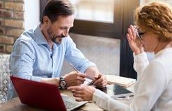 Couples d'une cinquantaine d'années travaillant sur l'ordinateur portable et prenant des notes image libre de droits