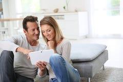 Couples d'une cinquantaine d'années websurfing avec le comprimé Image stock