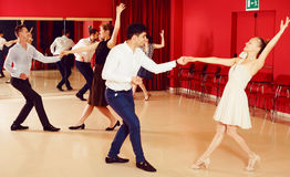 Couples dancing active swing. Adult dancing couples enjoying active swing in modern studio Royalty Free Stock Images