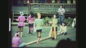 Couples Dancing Between Sticks. THAILAND, BANGKOK SAMPRAN RIVERSIDE, DECEMBER 1983. Two Couples With Colorful Costumes Performing The Lao Kratop Mai, The Bamboo stock footage