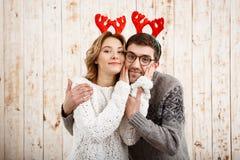 Couples dans de faux klaxons de cerfs communs souriant au-dessus du fond en bois Image libre de droits