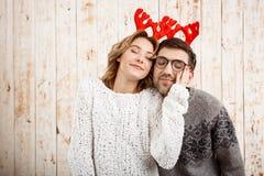 Couples dans de faux klaxons de cerfs communs souriant au-dessus du fond en bois Photo libre de droits