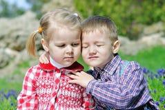 Couples dans de petits enfants d'amour sur le pré vert Photos stock