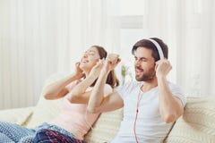 Couples dans des écouteurs se trouvant sur le sofa écoutant la musique dans la chambre Images stock