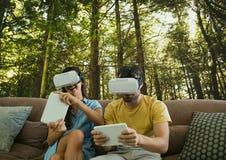 Couples dans des casques de VR jouant sur le fond en bois Photo stock
