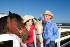 Couples dans des chapeaux de cowboy avec des chevaux - horizontaux Image stock