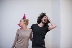 Couples dans des chapeaux de partie soufflant dans le sifflement Photographie stock