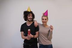 Couples dans des chapeaux de partie soufflant dans le sifflement Photo libre de droits