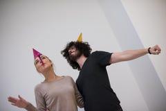 Couples dans des chapeaux de partie soufflant dans le sifflement Photos libres de droits