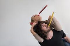 Couples dans des chapeaux de partie soufflant dans le sifflement Image stock