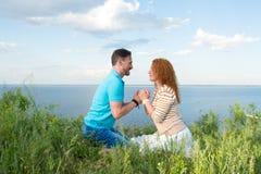 Couples dans des flirts d'amour sur la plage Le type tient les mains de fille et attire à se Portrait d'un couple heureux Image libre de droits