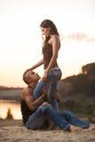 Couples dans des jeans sur la plage Image libre de droits