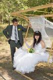Couples dans des jeunes mariés d'amour sur l'oscillation en parc Photographie stock libre de droits
