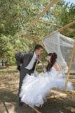 Couples dans des jeunes mariés d'amour sur l'oscillation en parc Photos stock