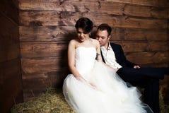 Couples dans des leurs vêtements de mariage dans la grange avec le foin Images stock