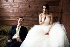 Couples dans des leurs vêtements de mariage dans la grange avec le foin Photo stock