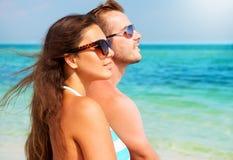 Couples dans des lunettes de soleil sur la plage Images libres de droits