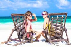 Couples dans des lunettes de soleil sur le canapé du soleil sur tropical Photos stock