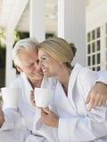 Couples dans des peignoirs avec des tasses sur la véranda Images stock