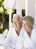 Couples dans des peignoirs avec des tasses sur la véranda Photos stock