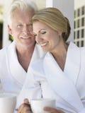 Couples dans des peignoirs avec des tasses sur la véranda Photographie stock libre de droits