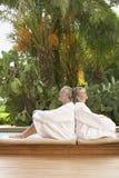Couples dans des peignoirs se reposant de nouveau au dos par la piscine Images libres de droits