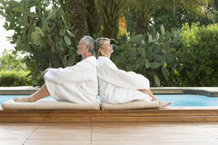 Couples dans des peignoirs se reposant de nouveau au dos par la piscine Photos stock