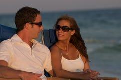 Couples dans des présidences de plage Photos stock