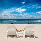 Couples dans des présidences de plage retenant des mains Image libre de droits