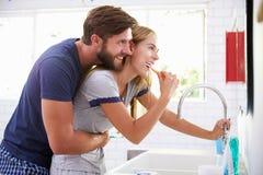 Couples dans des pyjamas brossant des dents dans la salle de bains Photographie stock