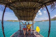 Couples dans des vêtements bleus sur une plage tropicale Photos libres de droits