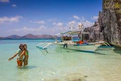 Couples dans des vêtements bleus sur une plage tropicale Photo stock