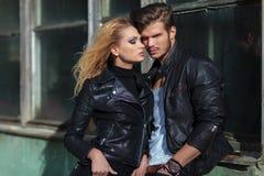 Couples dans des vestes en cuir posant contre un vieux bâtiment Image libre de droits
